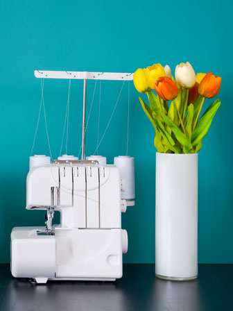 serger and a vase of tulips on a black table
